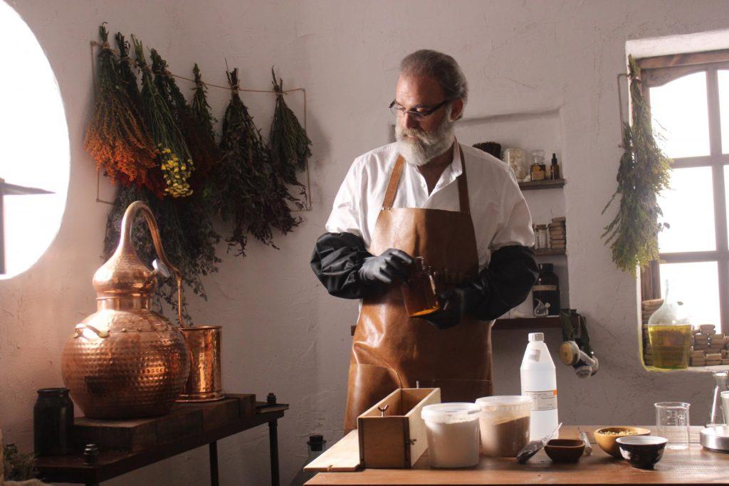 Бородатый мужчина в фартуке в процессе работы