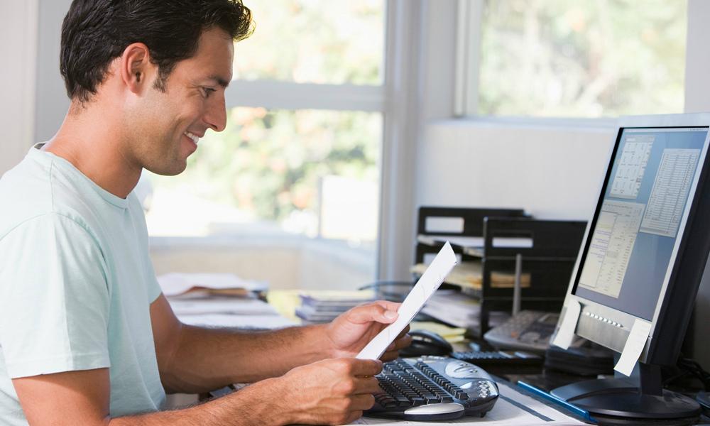 Мужчина читает документ у компьютера