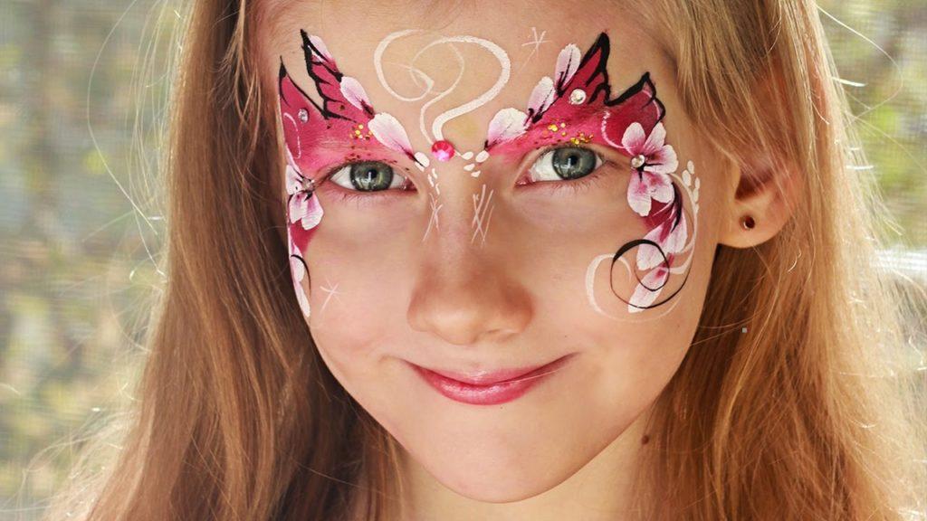 Аквагрим на лице у рыжеволосой девочки