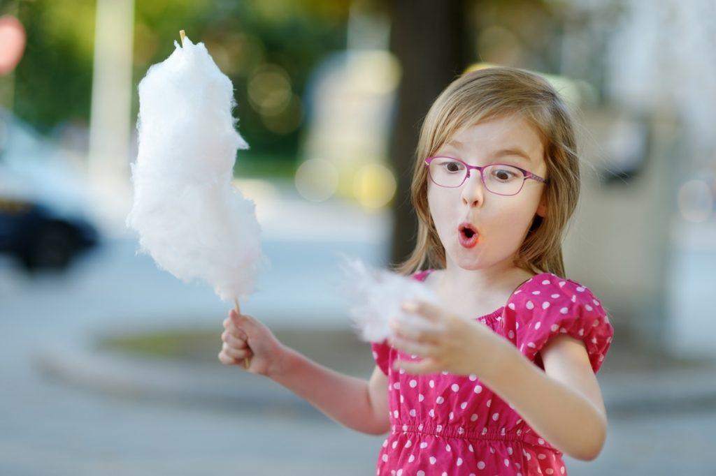 Ребенок с сахарной ватой на палочке