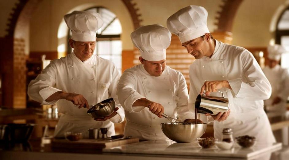 Мужчины в форме кондитеров что-то готовят