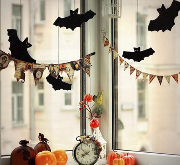 Оформление окна магазина флажками и чёрными летучими мышами на Хэллоуин