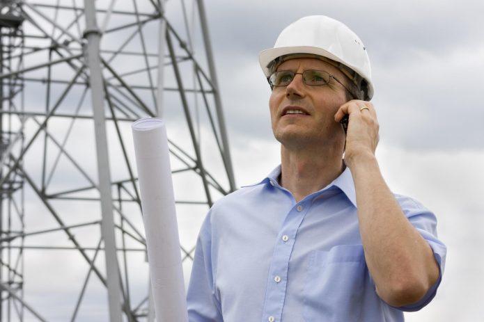 Мужчина в каске разговаривает по мобильному телефону