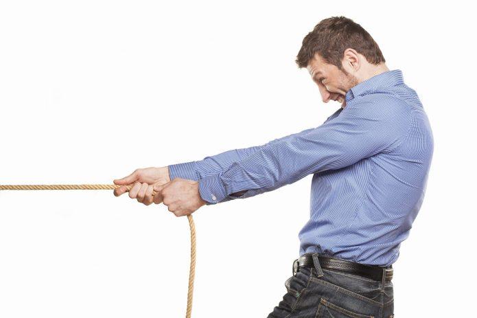 Мужчина тянет верёвку
