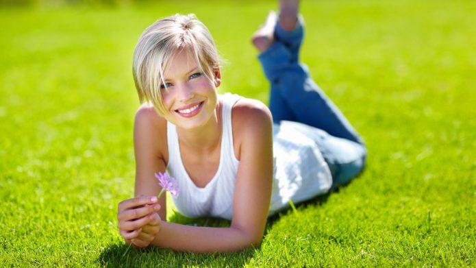 Девушка лежит на траве с цветком в руке