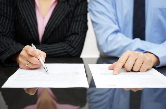 Женщина и мужчина изучают договор
