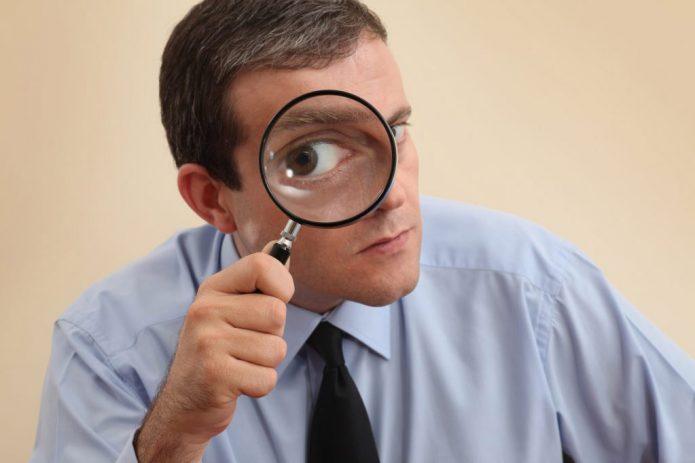 Мужчина смотрит через увеличительное стекло
