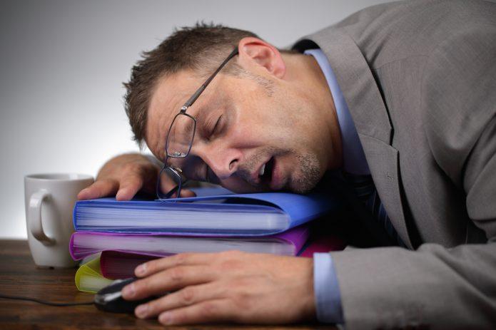 Мужчина спит на папках