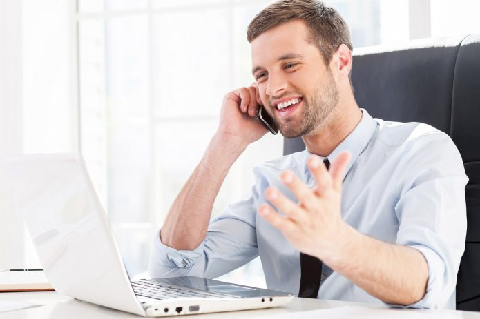 Мужчина говорит по телефону, глядя в ноутбук