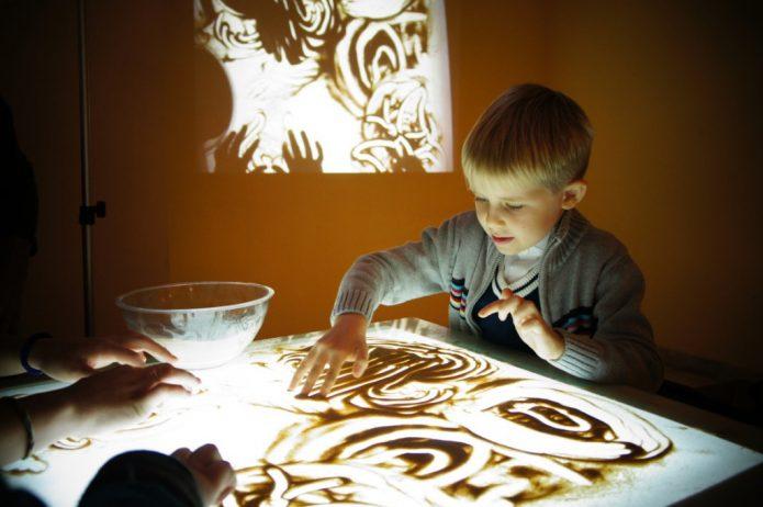 Мальчик занимается созданием картин из песка