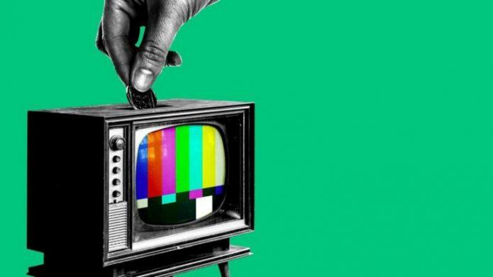 Рука опускает монету в телевизор