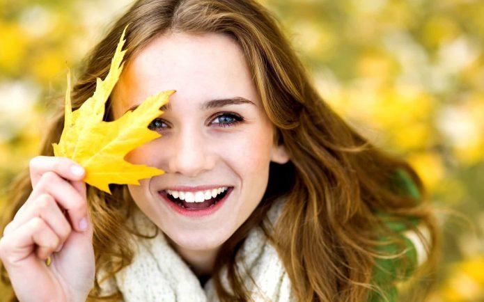Улыбающаяся девушка с осенним листом