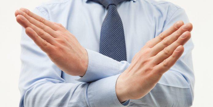 Человек скрестил кисти рук перед грудью