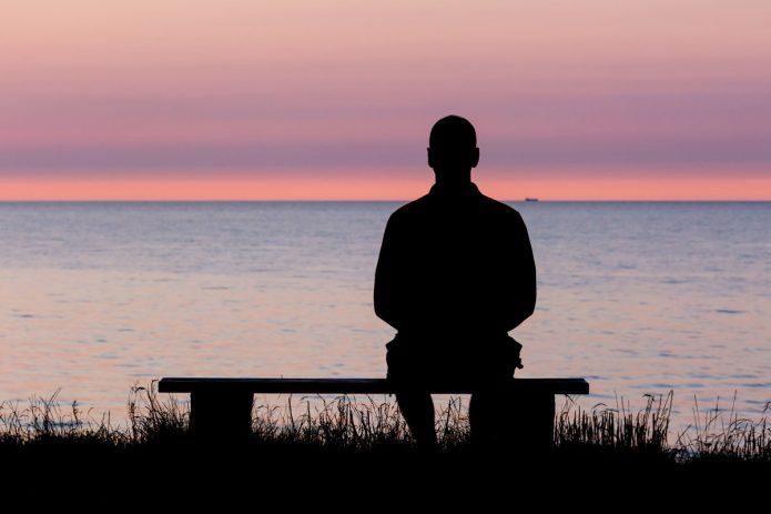 Человек сидит у воды
