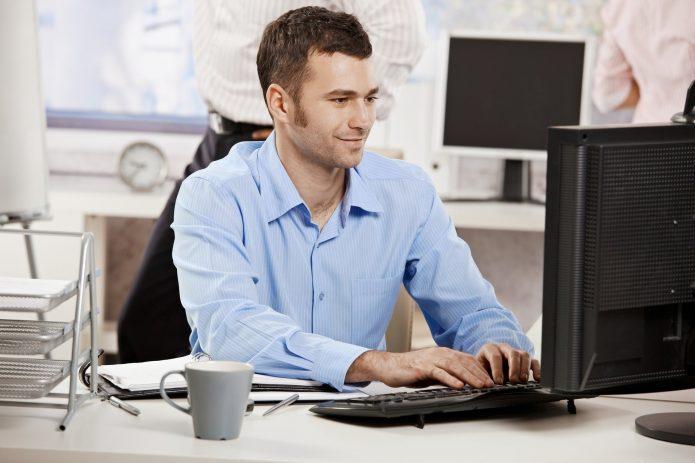 Мужчина смотрит на монитор и улыбается