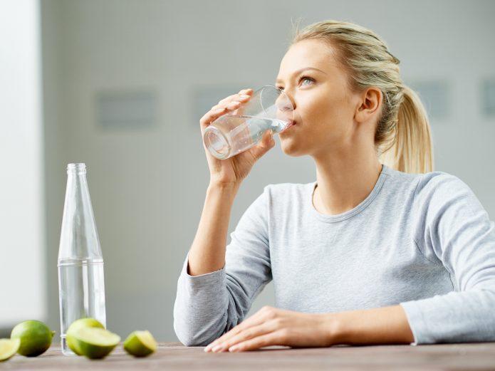 Девушка пьёт воду, чтобы не заснуть после бессонной ночи