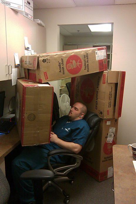 Спящий на работе среди коробок