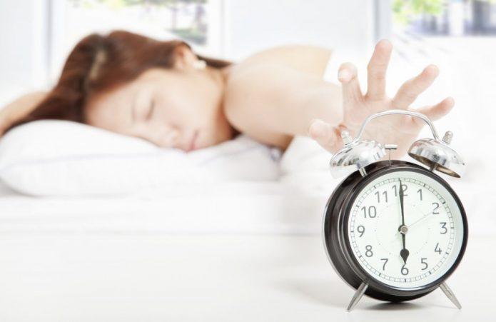 Женщина тянется рукой к будильнику