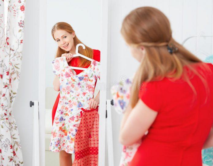 Девушка выбирает одежду перед зеркалом