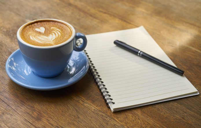 Чашка кофе и блокнот с ручкой