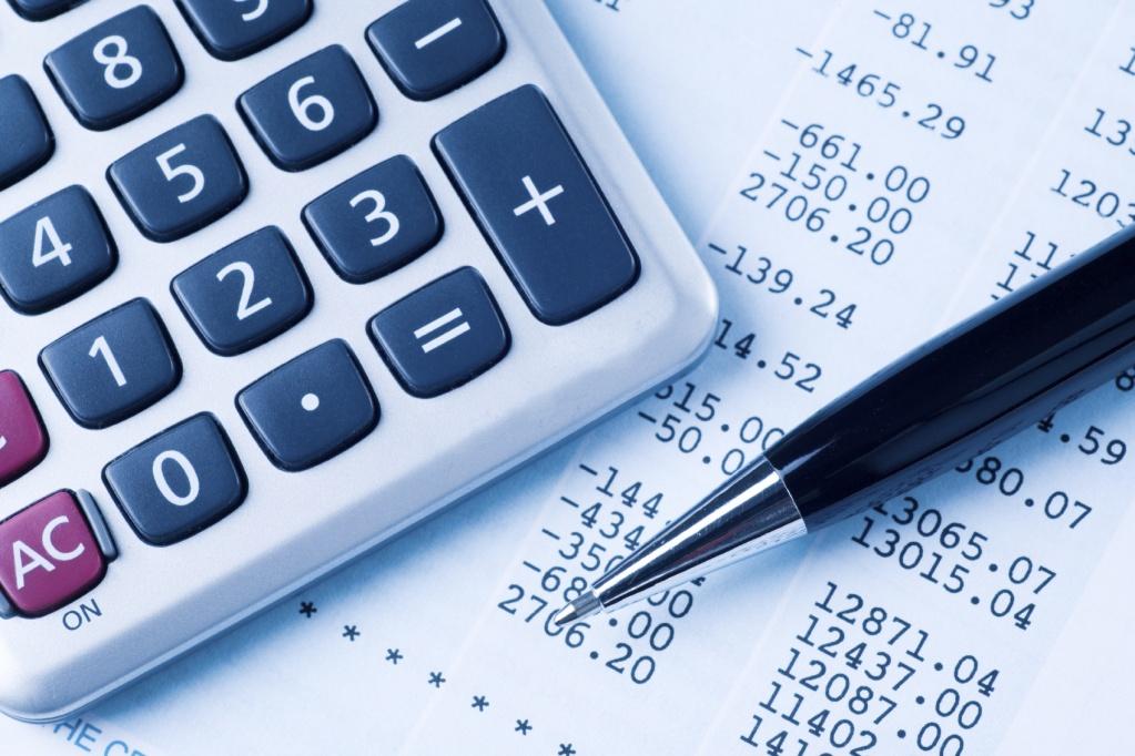 Калькулятор и ручка на фоне документа с цифрами