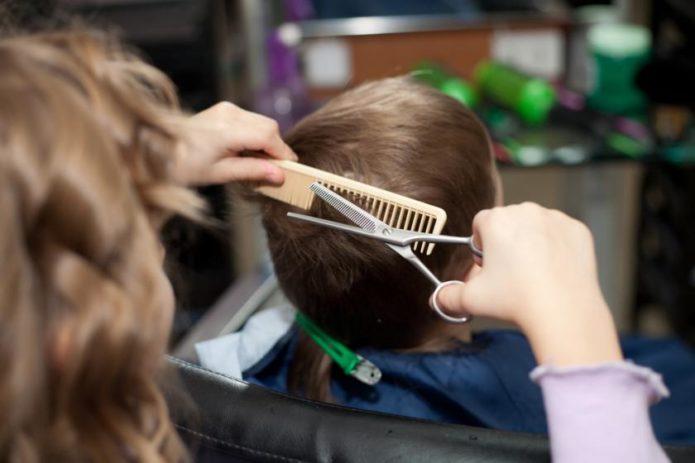 Парикмахер стрижёт ребёнка