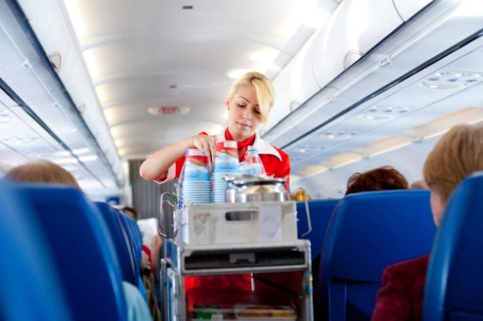 Стюардесса подаёт напитки пассажирам