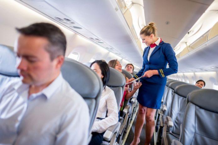 Стюардесса помогает пассажиру