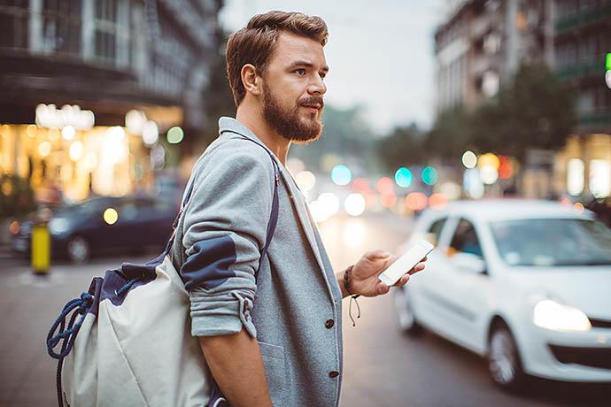 Парень с мобильным телефоном в чужом городе
