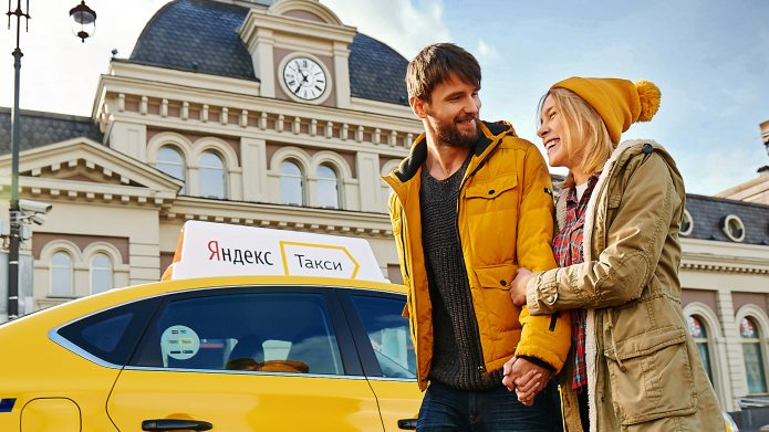 Девушка и парень на фоне вокзала и машины Яндекс Такси