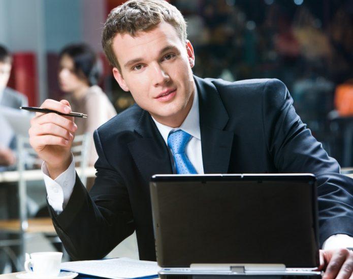 Мужчина в деловом костюме держит ручку