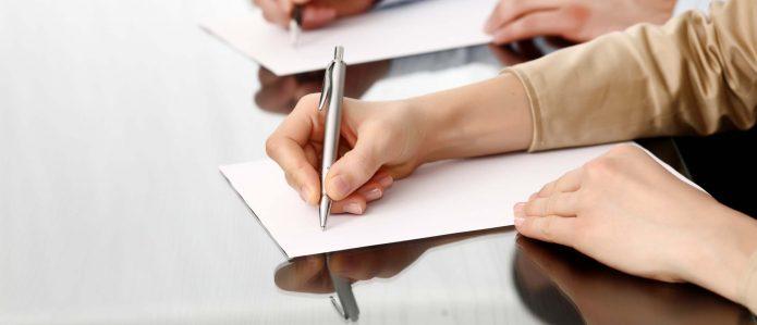 Рука пишет на листе бумаги