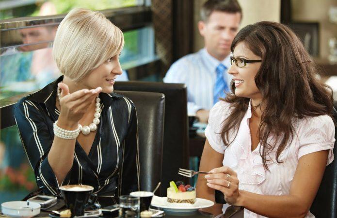Две девушки общаются за столиком в кафе