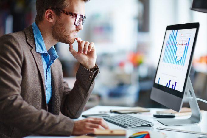 Молодой человек в очках работает на компьютере