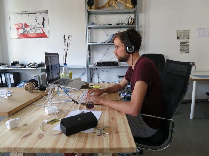 Программист в наушниках работает на ноутбуке