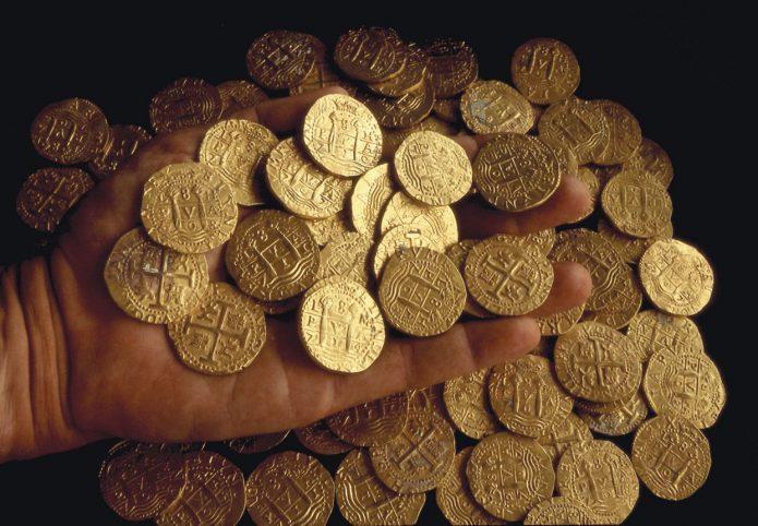 золотые монеты в руке