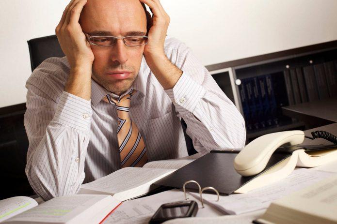 Уставший человек за офисным столом