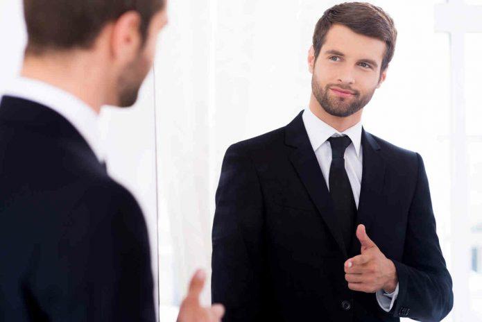 Мужчина смотрит на своё отражение в зеркале