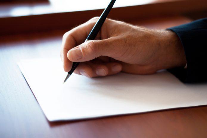 Человек собирается писать что-то на листе бумаги