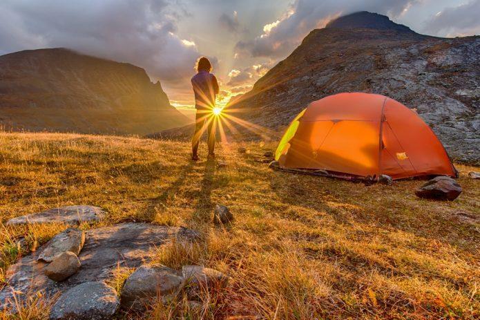 Мужчина в горах с палаткой
