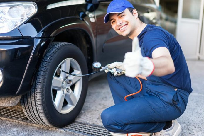Шиномонтажник проверяет давление в шинах