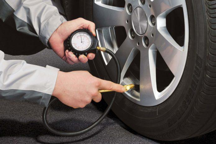 Мужчина проверяет давление в шинах