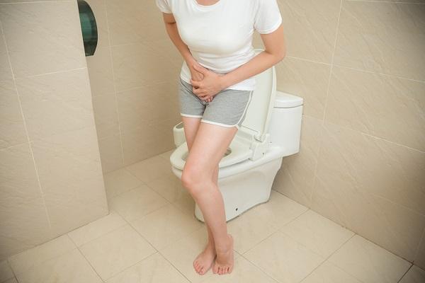 Девушка в туалете держится за живот