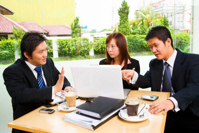 Японские бизнесмены совещаются за столом в кафе