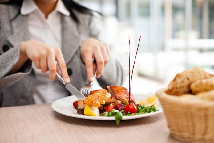 Женщина ест блюдо в ресторане