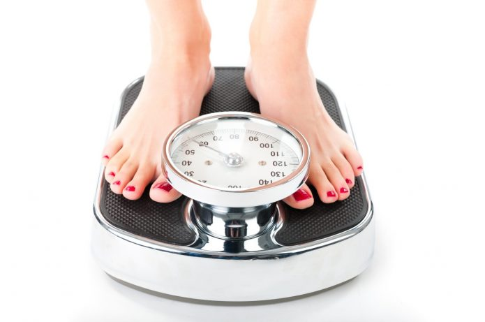 Женщина стоит на весах