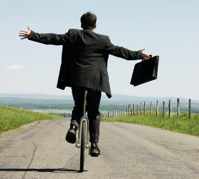 Мужчина едет с работы на велосипеде