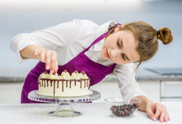 Девушка украшает торт