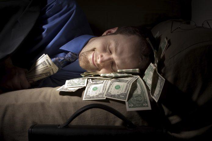 мужчина спит на деньгах